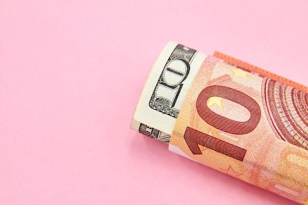 Un rouleau de billets en euros et en dollars américains avec copie espace