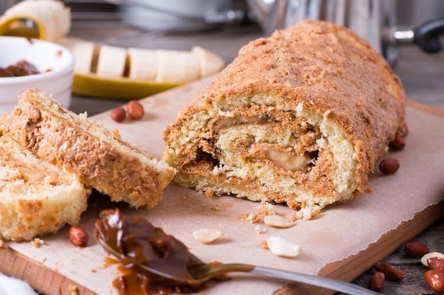 Rouleau de biscuit maison avec crème, banane et cacahuètes sur une table en bois