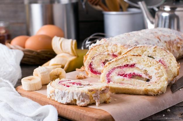 Rouleau de biscuits sucrés faits maison avec de la crème et des fruits sur une table en bois