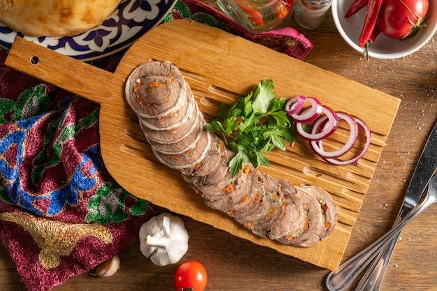 Rouleau de boeuf au fromage suluguni, carottes, herbes, noix, épices, coriandre et oignon rouge, haché et servi sur une planche à découper en bois.