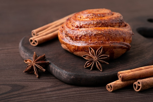 Rouleau à la cannelle sur une planche à découper brune avec une étoile d'anis et des bâtons de cannelle autour