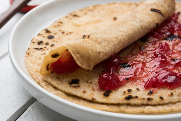 Rouleau de chapati avec ketchup de tomate ou gelée de confiture de fruits avec un visage souriant, menu préféré des enfants indiens pour la boîte de tiffin de l'école, mise au point sélective