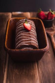Rouleau de chocolat savoureux avec fraise sur le dessus