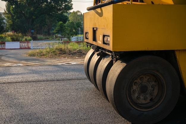 Rouleau compresseur jaune à fortes vibrations ou compacteur de sol travaillant sur une route de chaussée en asphalte mélangé à chaud sur un chantier de construction