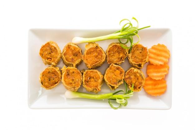 Rouleau de crabe frit dans une assiette blanche