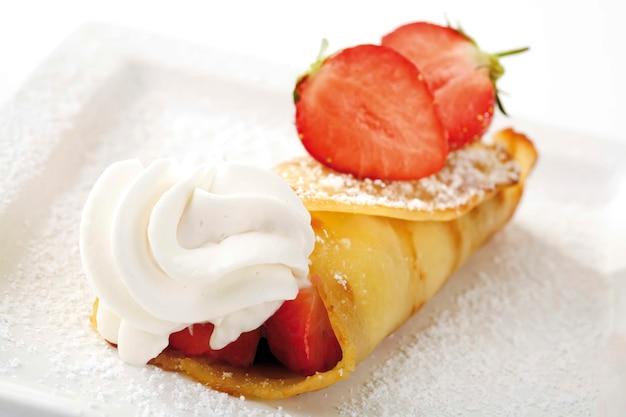 Rouleau de crêpes aux fraises sur fond blanc, gros plan