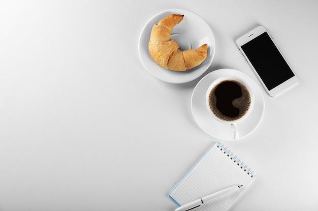 Rouleau de croissant savoureux avec tasse de café et téléphone sur une surface blanche