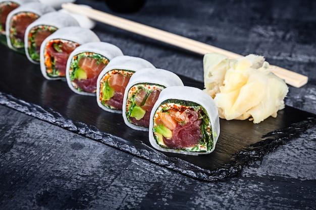 Rouleau de daikon aux crevettes au saumon et caviar tobico servi sur une assiette en pierre noire avec sauce soja et gingembre