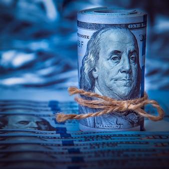 Un rouleau de dollars sur le fond de billets de cent dollars dispersés dans la lumière bleue.