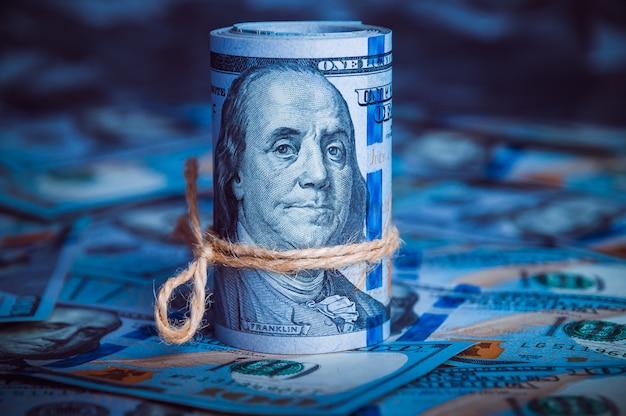 Un rouleau de dollars avec des pièces de monnaie sur le fond de billets dispersés de cent dollars