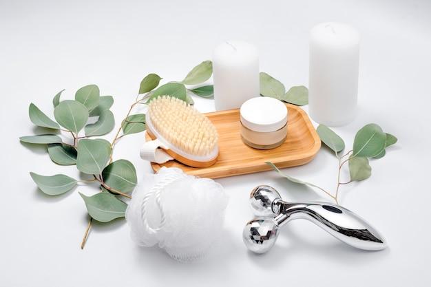 Rouleau facial, brosse de massage, crème pour le visage, gant de toilette et bougies aux feuilles d'eucalyptus naturelles sur fond clair.