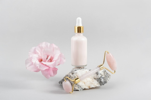 Rouleau facial en cristal de quartz rose, flacon compte-gouttes cosmétique sur pierre et belle fleur sur fond gris. massage du visage pour un lifting naturel, concept de beauté vue de face.