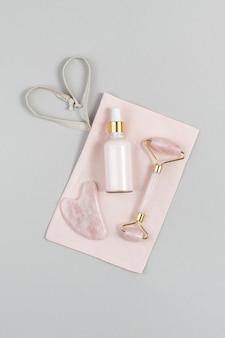 Rouleau facial en cristal de quartz rose, outil de massage gua sha et collagène anti-âge, sérum en bouteille de verre sur sac en tissu rose, fond gris. massage du visage pour un lifting naturel, concept de beauté vue de dessus.