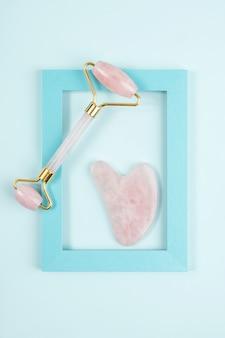 Rouleau facial en cristal de quartz rose et outil de massage jade gua sha dans un cadre sur fond bleu. massage du visage anti-âge pour un soin naturel liftant et tonifiant à domicile. concept de beauté vue de dessus.