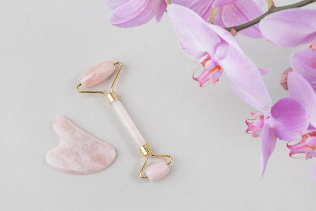 Rouleau facial en cristal de quartz rose, outil de massage jade gua sha et fleur d'orchidée naturelle sur fond gris. massage facial anti-âge pour un lifting naturel et un traitement tonifiant à domicile.