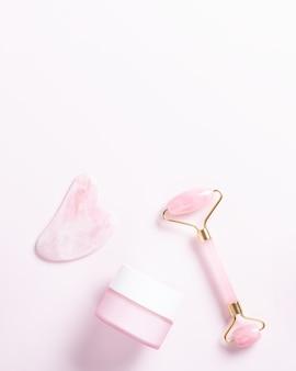 Rouleau facial, gua sha et crème hydratante aux feuilles vertes. cosmétiques naturels et outils faciaux sur rose. rouleau de beauté en quartz rose, coeur gua sha à plat. outils pour les routines de soins de la peau, vue de dessus