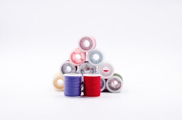 Le rouleau de fil de couleur rouge et bleu profond placé devant un groupe de fil coloré