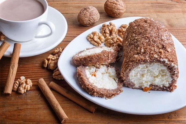 Rouleau de gâteau au lait caillé et aux noix isolé sur du bois brun