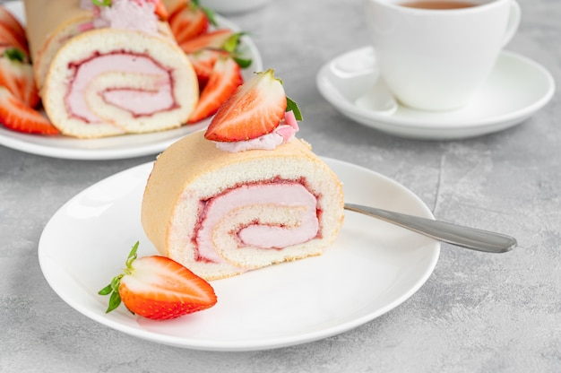 Rouleau de gâteau aux fraises fraîches, confiture et fromage à la crème sur une plaque blanche