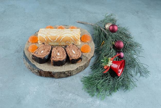 Rouleau de gâteau sur un plateau avec une branche de pin décorée sur du marbre.