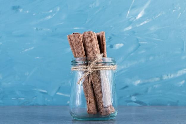 Rouleau de gaufrette au chocolat savoureux dans un bocal sur la surface en marbre
