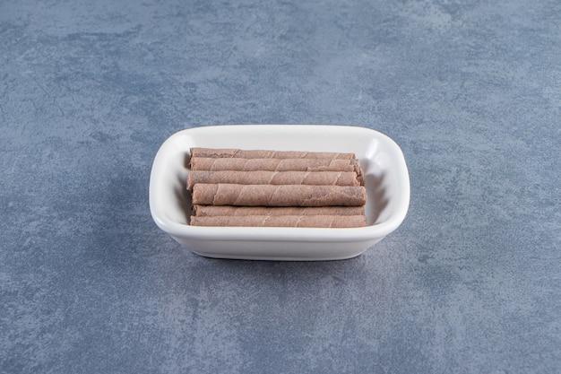 Rouleau de gaufrettes au chocolat délicieux dans un bol sur la surface en marbre