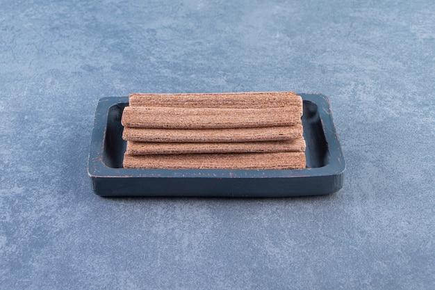 Rouleau de gaufrettes au chocolat savoureux dans une assiette en bois sur la surface en marbre