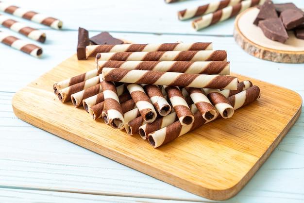 Rouleau de gaufrettes au chocolat sur la surface du bois