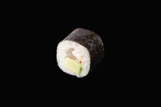 Rouleau hosomaki avec anguille, avocat isolé sur fond noir