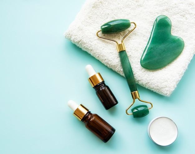 Rouleau de jade de massage du visage avec produit cosmétique sur fond vert pastel