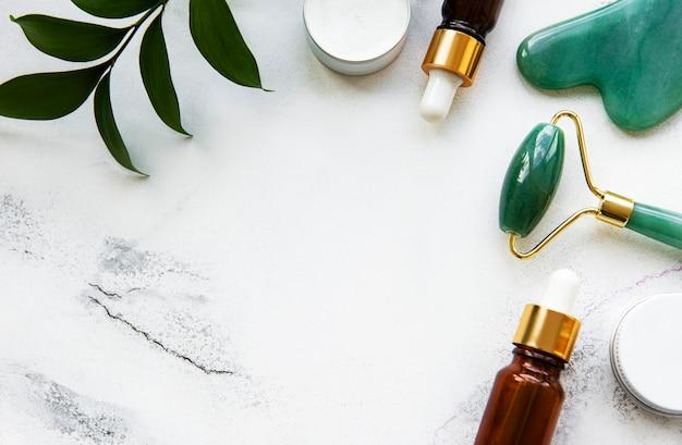 Rouleau de jade de massage du visage avec produit cosmétique sur table en marbre blanc