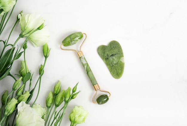 Rouleau de jade pour massage du visage. outils de massage du visage gua sha vert sur fond blanc en marbre avec espace de copie à plat. traitement anti-âge, liftant et tonifiant, acupression. fleurs d'eustoma