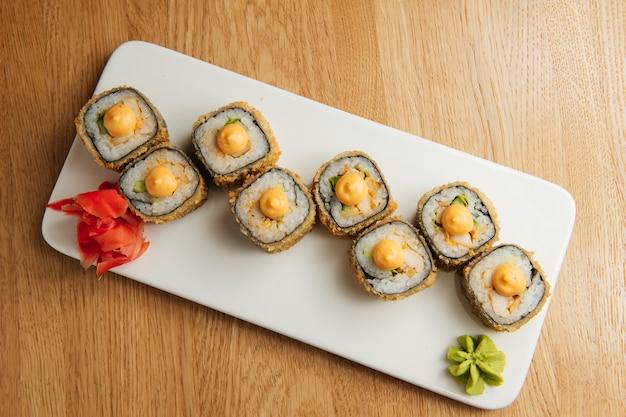 Rouleau japonais en tempura avec sauce sur plaque blanche. morceaux de rouleaux chauds asiatiques