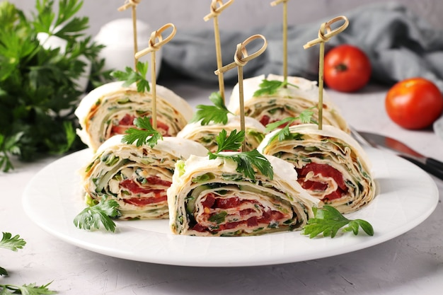 Rouleau de lavash avec concombres, tomates, fromage et persil sur fond gris. apéritif festif.