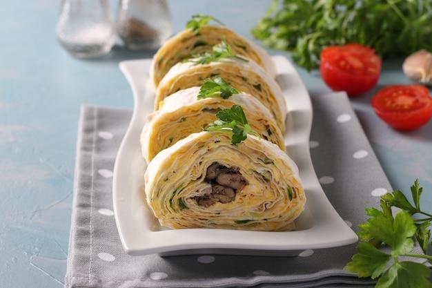 Rouleau de lavash avec sprats, fromage à la crème, concombre et œufs sur fond bleu clair. fermer