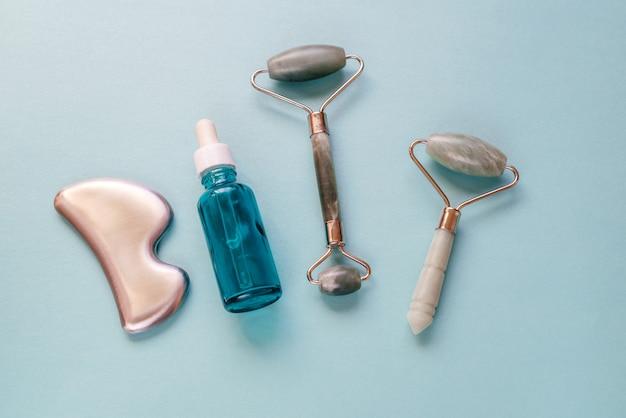 Rouleau de massage en jade guasha, gua sha en acier et bouteille de sérum sur fond bleu. spa relax, soin du visage et de la peau