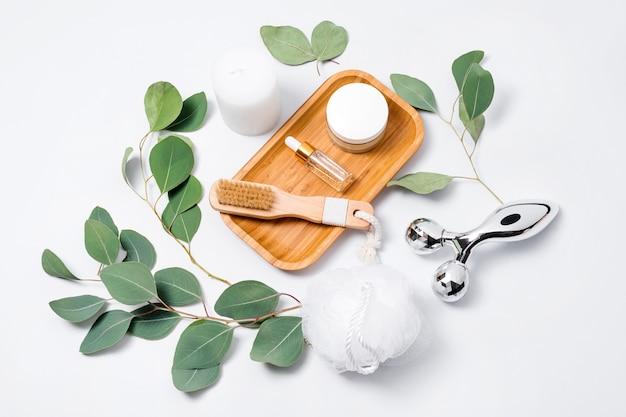 Rouleau de massage et pinceau, huile essentielle ou sérum cosmétique et crème cosmétique aux feuilles d'eucalyptus sur fond blanc.