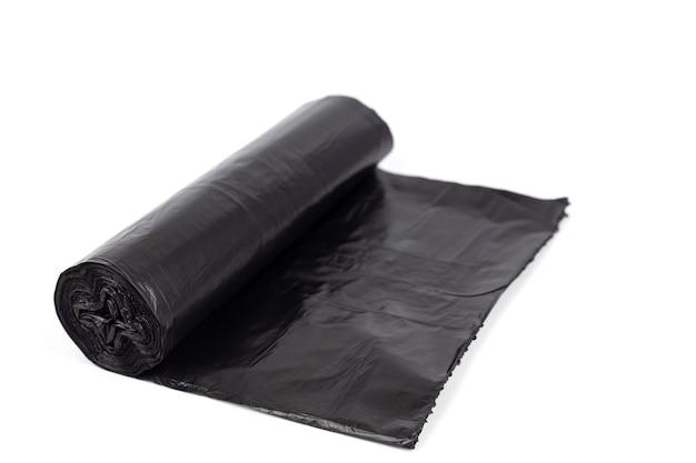 Rouleau noir de sacs à ordures en plastique isolé sur fond blanc.