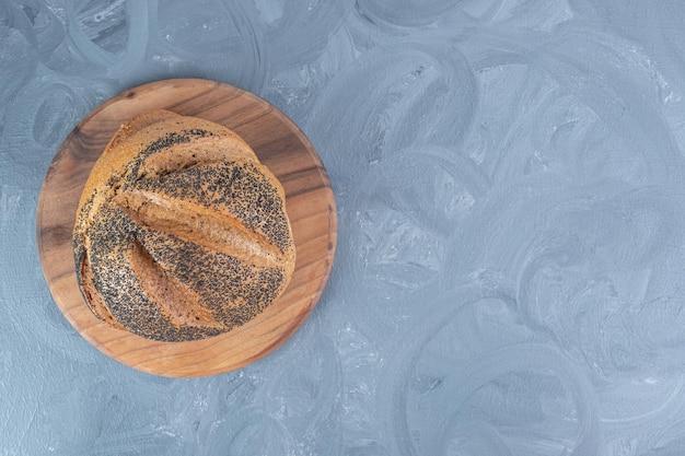 Rouleau de pain recouvert de graines de sésame noir sur fond de marbre.