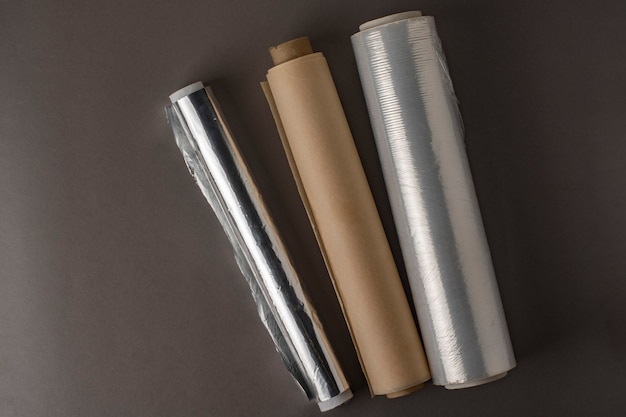 Un rouleau de papier d'aluminium, un rouleau de film alimentaire et un rouleau de papier sulfurisé.