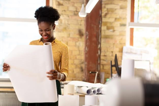 Rouleau de papier. belle travailleuse élégante à la peau foncée de l'agence d'édition tenant un rouleau de papier