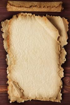 Rouleau de papier déplié sur une surface en bois, fond blanc