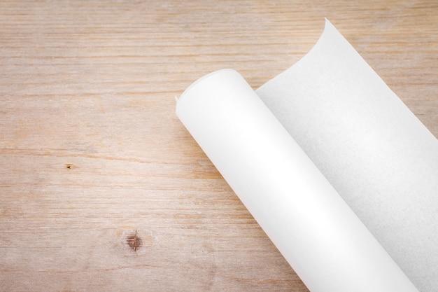 Rouleau de papier sur fond de table en bois. plan d'ingénieur pour les travaux préliminaires.