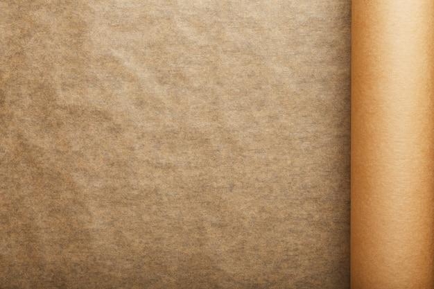 Un rouleau de papier parchemin brun déplié, pour la cuisson des aliments sur un fond sombre, vue de dessus.