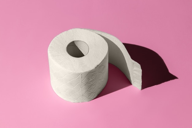 Rouleau de papier toilette blanc isolé sur un gros plan de fond rose. ombres dures du soleil à midi