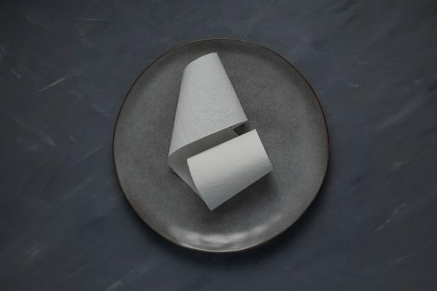 Un rouleau de papier toilette blanc sur une plaque grise