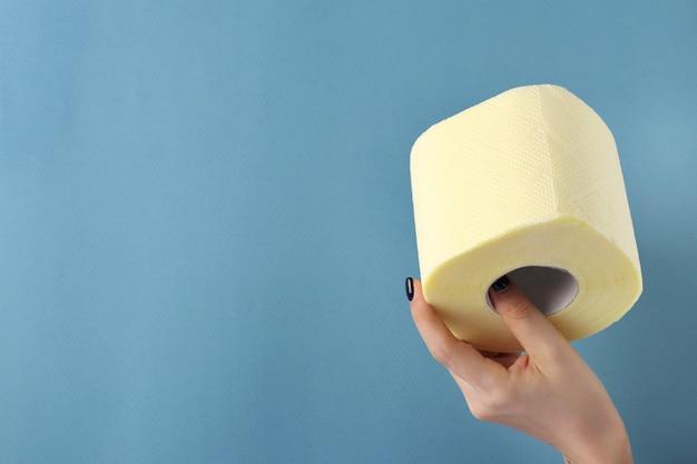 Rouleau de papier toilette dans une main féminine sur fond bleu avec un espace pour le texte, pandémie de covid-19, déficit, demande inattendue accrue