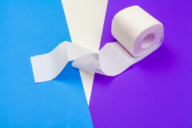 Rouleau de papier toilette sur fond de couleur bleue