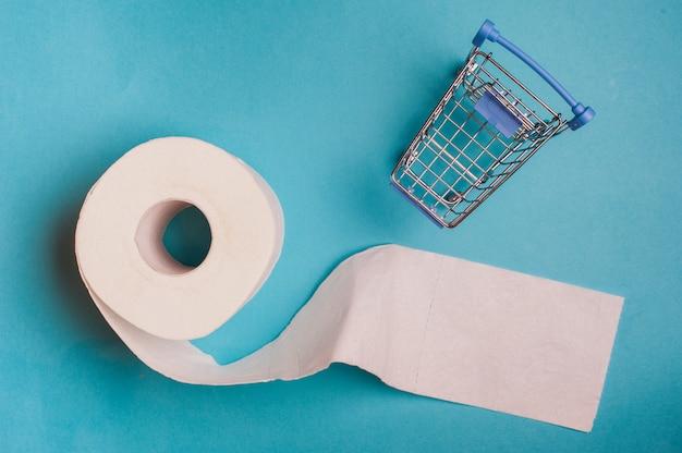 Rouleau de papier toilette et petit panier sur fond bleu.