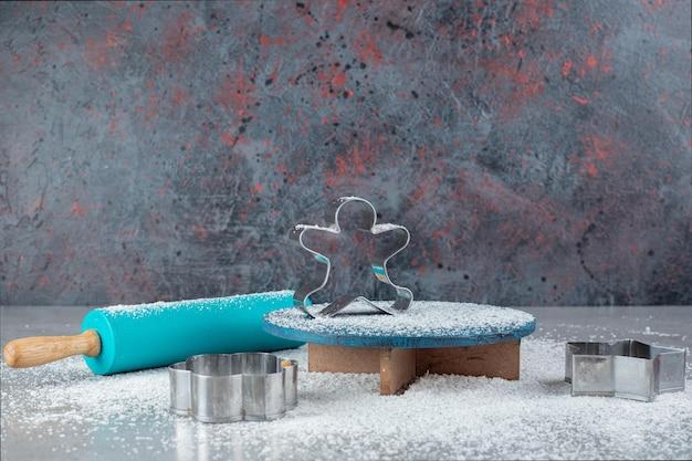 Rouleau à pâtisserie bleu, moules à biscuits, plateau et poudre de noix de coco sur une surface en marbre